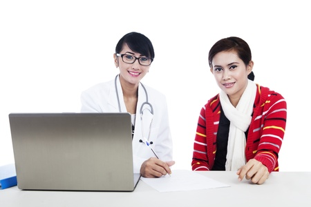 Interaction between doctor and patient using a laptop in studio photo