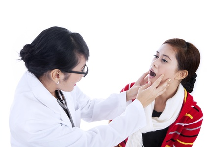 Female doctor checking her patient by asking her to open her mouth photo