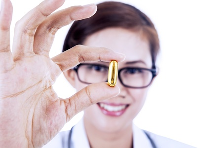 Female doctor holding a medicine pill in a close up version photo