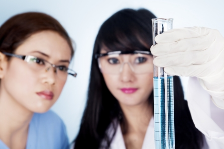 Female scientific research team holding a clear blue solution inside a flask in laboratory photo