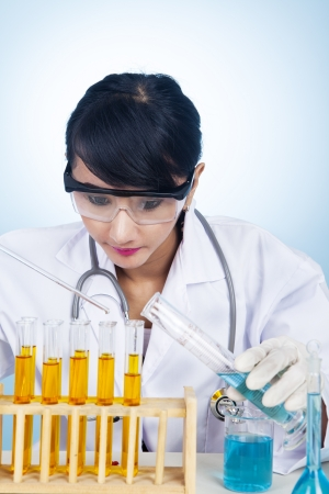 Female scientist is examining yellow and blue solutions in her lab photo
