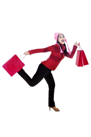 Excited woman shopper carrying shopping bags isolated in white photo
