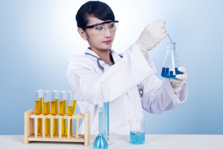 Female researcher working with blue chemical inside a flask Stock Photo - 15762949