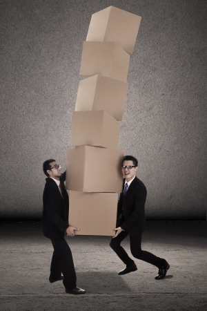 Two businessman is trying to balance plenty of boxes together photo