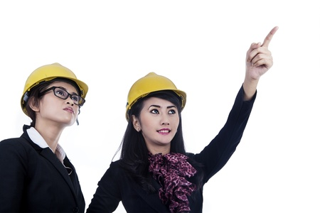 Two female architects wearing yellow helmet isolated in white photo