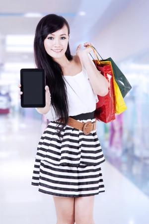 exibindo: Mulher asi?tica bonita que mostra a tela vazia de computador tablet, enquanto carregando sacolas de compras Banco de Imagens