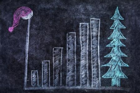 Chalk drawing of santa hat, bar chart and christmas tree on the blackboard photo