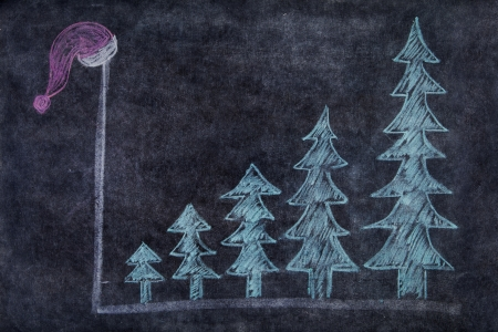 Chalk drawing on the blackboard with five christmas trees in upward shape showing profit during christmas season photo