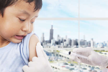 vaccines: A boy is scared looking at his arm because he