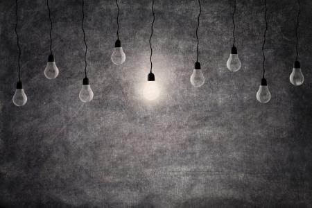 id�e lumineuse: Concept id�e lumineuse d'une ampoule rougeoyante de lumi�re devant le tableau noir vide, avec copie espace