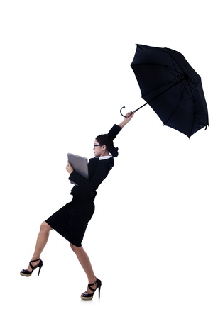 strong wind: Businesswoman is holding a laptop while a strong wind is blowing away her umbrella