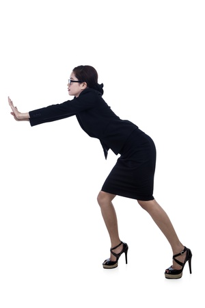 Businesswoman is pushing something or leaning to wall with white background photo