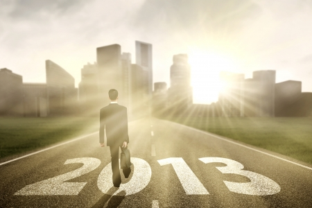 Businessman is walking on the road to embrace new year 2013 photo