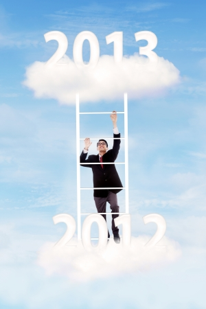 Businessman climbing upward on the stair of cloud from the year of 2012  to 2013 to gain his success Stock Photo - 16011266