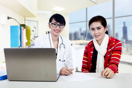 Both female doctor and patient are looking at the camera while explaining prescription via laptop photo
