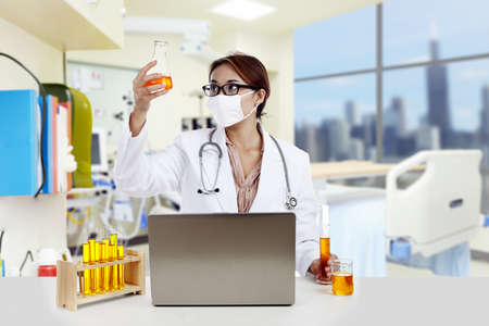 yellow yellow lab: Doctor with chemicals working on laptop in a clinic  Stock Photo