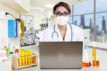 bata de laboratorio: Doctor con productos químicos trabajando en la computadora portátil en una clínica
