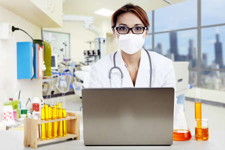 lab coat: Doctor with chemicals working on laptop in a clinic  Stock Photo