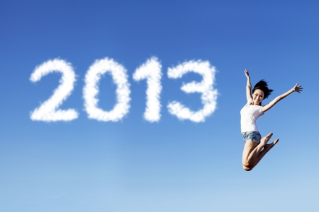 Woman jumping under clear blue sky with 2013 clouds next to her photo