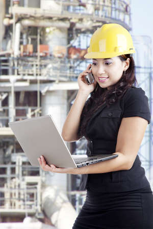 Young female contractor checking her plan on the laptop while talking on the phone  photo