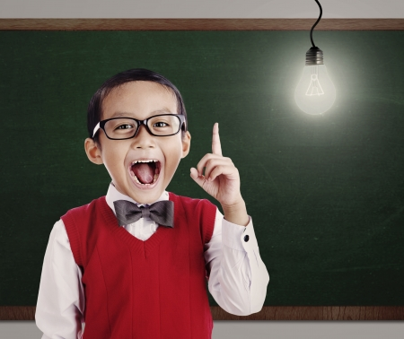 indian kid: Asian genius student with light bulb shot in a classroom