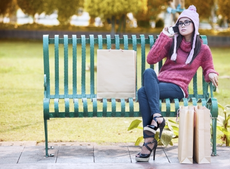 Portrait of shopping woman sitting on the bench with bags and talking on the phone  shot outdoor photo