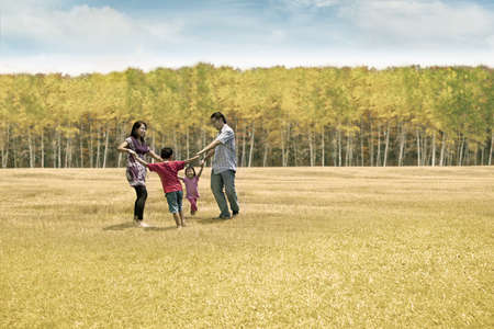 indonesian woman: Happy asian family playing on the field  They are running in circle  shot outdoor during autumn day Stock Photo