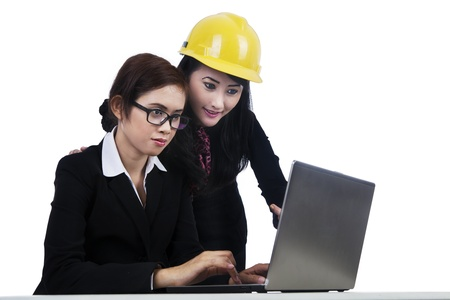 Two young architects working together on a laptop isolated in white photo