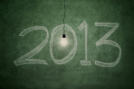 2013 new year concept  an electric light bulb glowing bright in front of blackboard symbolising good year Stock Photo - 16041039