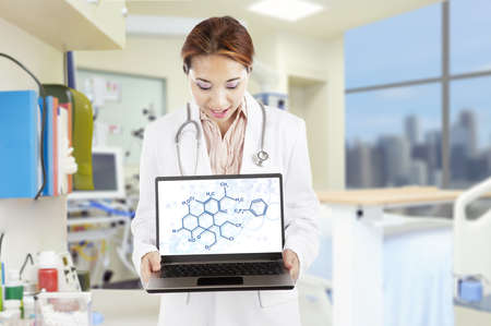 Portrait of female researcher showing chemistry formulas on the laptop at laboratory photo