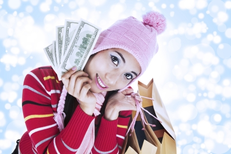 Portrait of fashionable woman holds money and shopping bag dressed for winter  shot over defocused light background photo