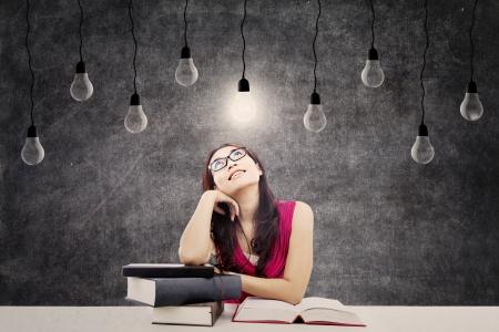 tanulás: Portré az intelligens női főiskolai hallgató, könyvekkel és fényes villanykörte a feje fölött, mint egy szimbólum a kiváló ötletek