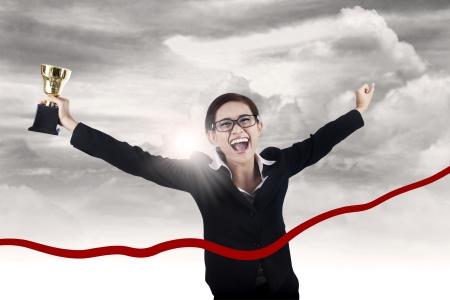 Empresaria celebra su victoria y corriendo a través de la cinta mientras se mantiene trofeo Foto de archivo