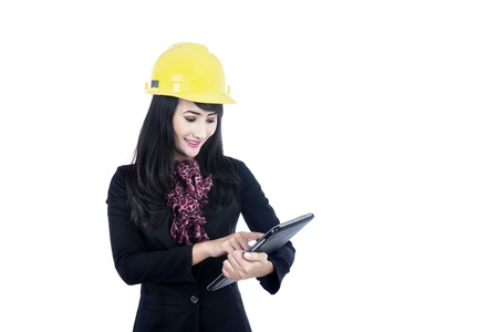 Female architect is smiling while touching her tablet isolated in white Stock Photo - 16085512