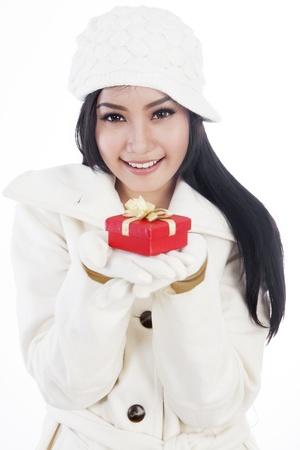 ropa de invierno: Retrato de mujer hermosa que desgasta la ropa de invierno que dan un regalo de Navidad. aislado sobre fondo blanco