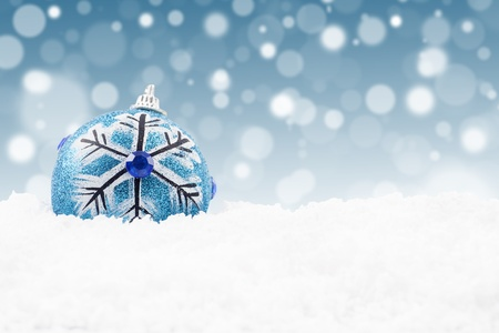 Blue christmas bauble on the snow with christmas lights background Stock Photo