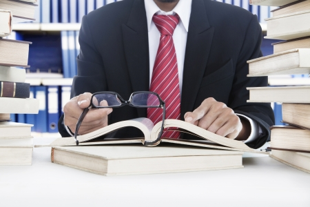 master degree: Unrecognizable business person with red tie reading a book in the library without glasses