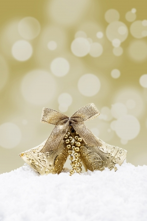 shinning light: Christmas bells on the snow with golden christmas lights background