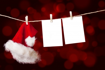 string together: A red christmas Santa hat is hanging on a string together with notes on defocused red lights