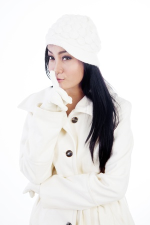 noiseless: Portrait of beautiful woman wearing winter clothes gesturing to be quiet. isolated on white Stock Photo