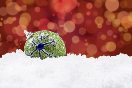 Green christmas ball on the snow with red christmas defocused light background photo