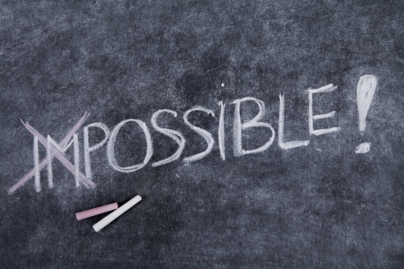 motivator: Text of impossible is nothing written on a blackboard