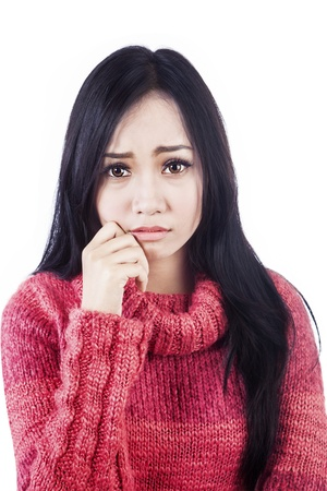 Portrait of sad woman wearing red sweater. isolated on white bakground photo