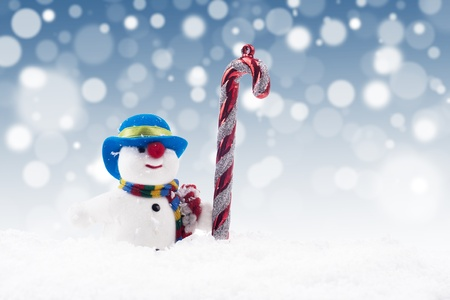 Snowman doll with candy cane on the snow with blue christmas light background Stock Photo - 16149508