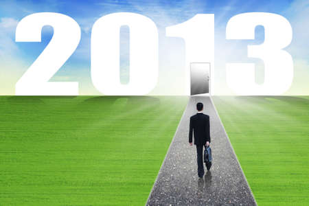 Businessman walks with suitcase on the path lead to the future in 2013 Stock Photo - 16149532