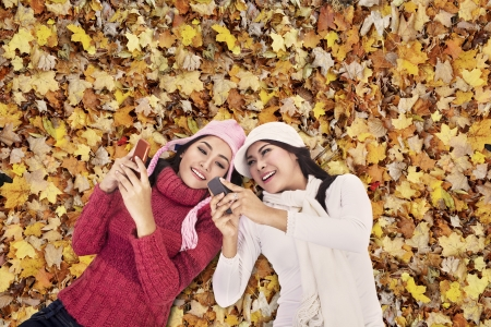 Closeup of young women wearing winter clothes playing mobile phone over autumn foliage photo