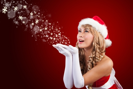 Beautiful blonde hair Mrs Santa Claus is wishing you all merry Christmas in red background photo