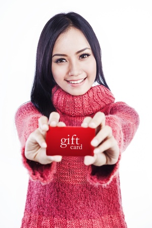 Portrait of excited woman wearing red sweater and showing a red gift card  isolated on white photo