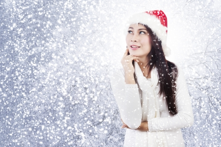 Portrait of happy dreaming christmas woman wearing winter clothes with falling snow photo