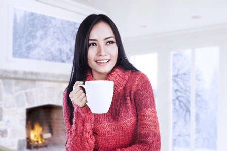 Beautiful young woman warming up with a hot cup of coffee near a fireplace at home photo